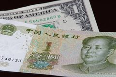 One chinese yuan banknote is above one american dollar. On black background royalty free stock images