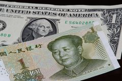 One Chinese yuan banknote above one american dollar on black background. One Chinese yuan banknote is above one american dollar on black background stock photo