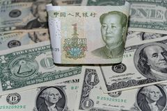 One Chinese yuan banknote against background of american dollars. One Chinese yuan banknote against american dollars laid out as a background stock photos