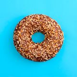 One chocolate donut on blue background top view close up stock photography
