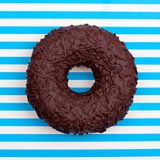 One chocolate donut on striped blue and white stripes background top view close up stock photography