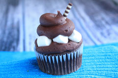 One chocolate marshmallow cupcake on a blue stand wooden background Royalty Free Stock Images