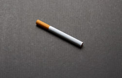 One cigarette of tobacco. On a dark background Royalty Free Stock Photo
