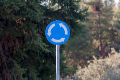 One circular roundabout metal sign. Before trees Royalty Free Stock Photos