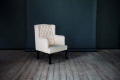 One classic armchair against a dark blue wall and Stock Photo