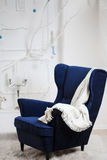 One classic armchair against a white wall and Royalty Free Stock Images
