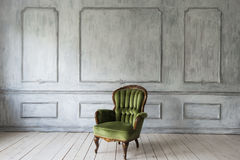 One classic armchair against a white wall and floor. Copy space stock image
