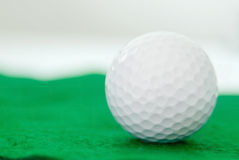 One clean new white golf ball on green artificial turf Stock Images
