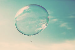 One clean soap bubble flying in the air, blue sky. Vintage Royalty Free Stock Photography
