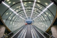 One cleaning staff person in orange coat on escalator at modern, futuristic architecture subway station, arched ceiling stock images