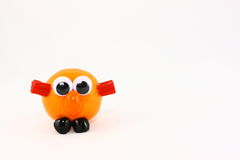 One Clementine With A Funny Face. One fresh clementine fruit decorated with assorted candies and plastic eyes to create a cute fun creature Stock Image