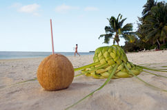 One coconut and sun hat on the sandy sea shore Royalty Free Stock Image