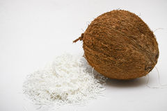 One coconut with white shredded pulp. One whole coconut with shredded white pulp, on white background Royalty Free Stock Photos