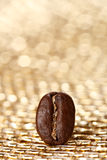 One coffee bean on golden glitter background Royalty Free Stock Image