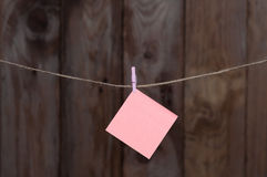 One colored piece of paper hanging on a rope Royalty Free Stock Image