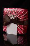 One colorful gift box. One colorful red gift box with brown ribbon  isolated on black background Stock Photo