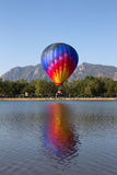 One colorful hot air balloon dipping into a lake. One multicolor Hot air balloon dipping into Prospect Lake at Memorial Park with the front range in the stock image