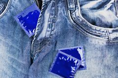 One condom in zipper and two condoms scattered on blue jeans stock image