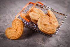 One cookie in form of heart near lot of cookies in metal chrome market basket with orange rubber handles on old gray cemen stock photos