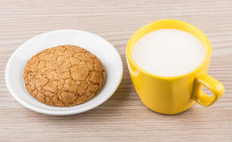One cookie in saucer and yellow cup of milk Royalty Free Stock Images