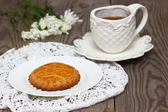 One cookie with tea. Baked cookie with tea and flowers. Shallow DOF royalty free stock photos