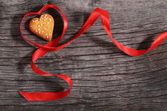 One cookies and heart shaped red ribbon Royalty Free Stock Photos