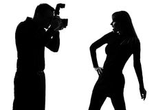 One couple man photographer and woman model. One caucasian couple man photographer photographing and woman fashion model posing in studio silhouette isolated on stock photography