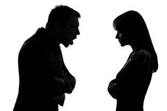 One couple man and woman screaming shouting dipute. One caucasian couple men and women face to face screaming shouting dipute in studio silhouette isolated on Stock Images