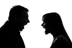 One couple man and woman screaming shouting dipute. One caucasian couple men and women face to face screaming shouting dipute in studio silhouette isolated on Stock Photos