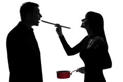 One couple man and woman tasting cooking sauce pan. One caucasian couple men and women tasting cooking sauce pan in studio silhouette isolated on white Stock Image