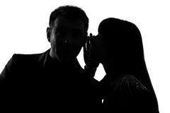 One couple man and woman whispering at ear. One caucasian couple men and women  whispering at ear in studio silhouette isolated on white background Stock Photos