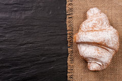 One croissant sprinkled with powdered sugar on black stone background with copy space for your text. Top view Stock Photos
