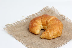 One croissant on spuare frayed burlap Royalty Free Stock Photos
