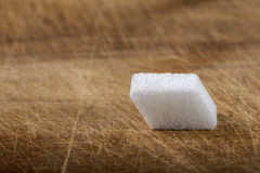 One cube of sugar on wood Royalty Free Stock Photography