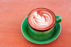 One cup of cappuccino with latte art of Living Coral color on wooden background, greenery ceramic cup, place for text. royalty free stock photos
