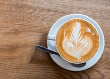 One cup of cappuccino with latte art on wooden table, white ceramic cup, top view. Cafe culture. stock photography
