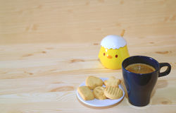 One Cup of Coffee and a Plate of Butter Cookies served on the Wooden Table with Cute Little Chick Sugar Pot Royalty Free Stock Photography