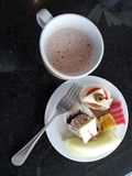 One cup of tea and plate of food for breckfast. There are cheese, fruit, cakes and sardines Stock Photography