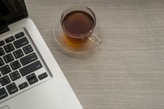 One cup of tea is on the right side of the laptop stock image