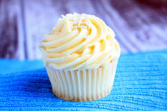 One cupcake on a blue stand wooden background Royalty Free Stock Image