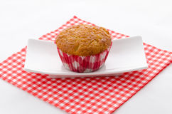 One cupcake on a plate. One cupcake on a red patterned napkin and plate Stock Photo