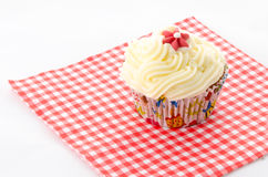 One cupcake - red patterned napkin. One cupcake buttercream on a red patterned napkin and flower Royalty Free Stock Image