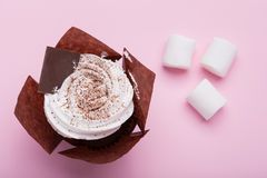 One cupcake with white cream on a pink background, beside scattered marshmallows, a concept of a feast and dessert, a stock image