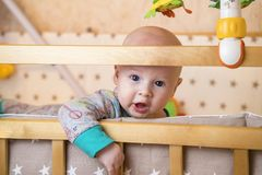 One curious caucasian infant baby boy with blue eyes is trying to climb out from child crib Stock Images