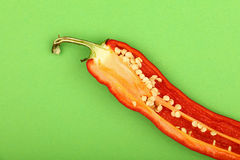 One cut red hot chili pepper on green background Stock Photos