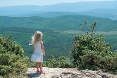 One cute blonde girl in countryside on a high rock among the mountains on a bright sunny day