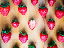 One cutted strawberry in an srranged pattern of strawberries on Stock Photos