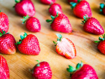 One cutted strawberry in an srranged pattern of strawberries on. A wooden board, difference expression Royalty Free Stock Image