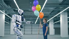 Modern robot gifts balloons to a little girl, side view. One cyborg gifts many balloons to a girl stock video footage