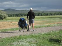 One cyclist go to road. Bicycle travel. One cyclist go to road. Bike Touring royalty free stock photography